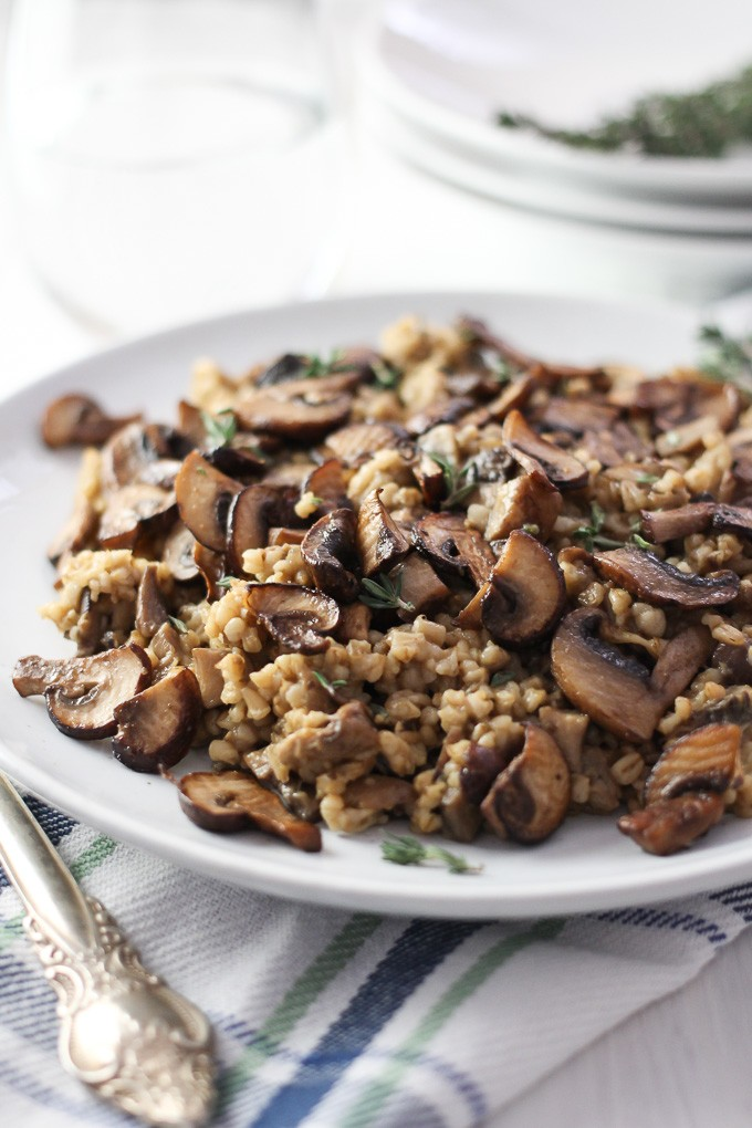 Close-up side view of the Savory Steel Cut Oats with Mushrooms and Thyme on a white plate placed on a kitchen towel.