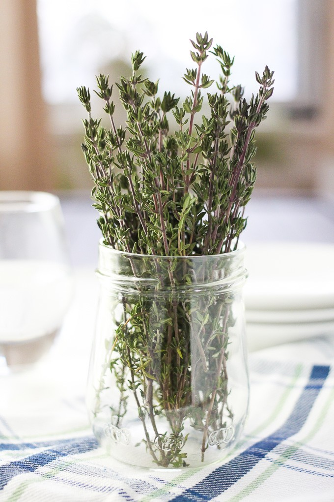 Close-up side view of a bunch of thyme in a jar standing on a kitchen towel.