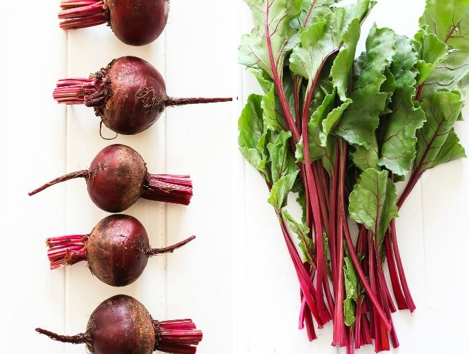 Two side-by-side top view images - on the left are beetroots with greens cut off, on the right is a bunch of beet greens.