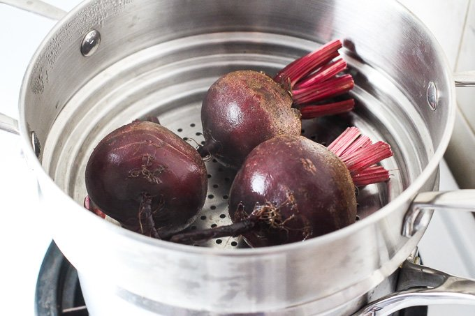 Three small beets in a steamer basket.