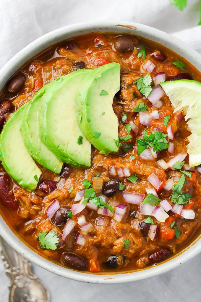 Tuna chili in a bowl garnished with avocado and red onion.