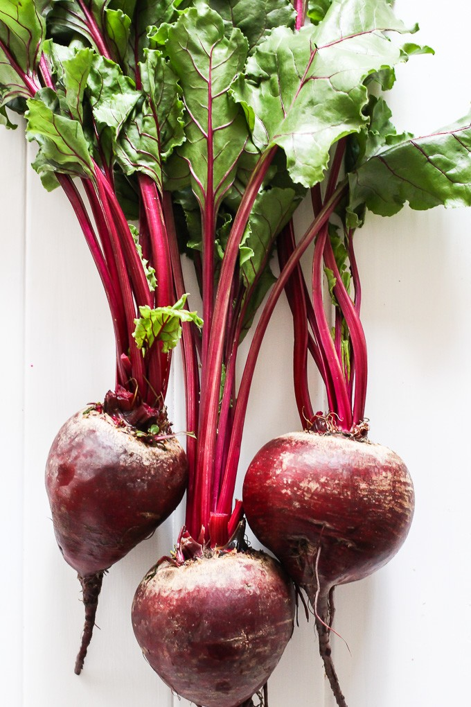 Three red beets with greens on a white background.