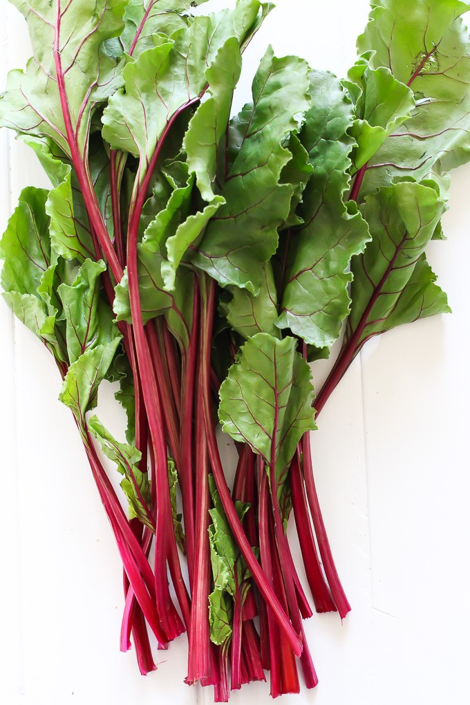 A bunch of beet greens on a white background.