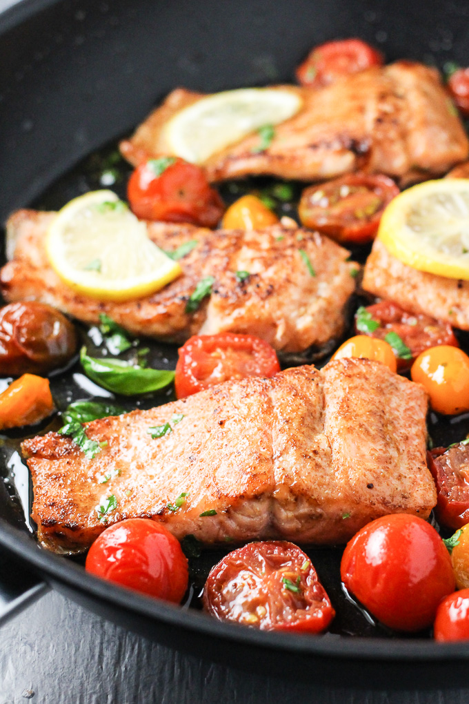 Close-up side view of the pan fried rainbow trout with cherry tomatoes and lemon slices in a black pan.
