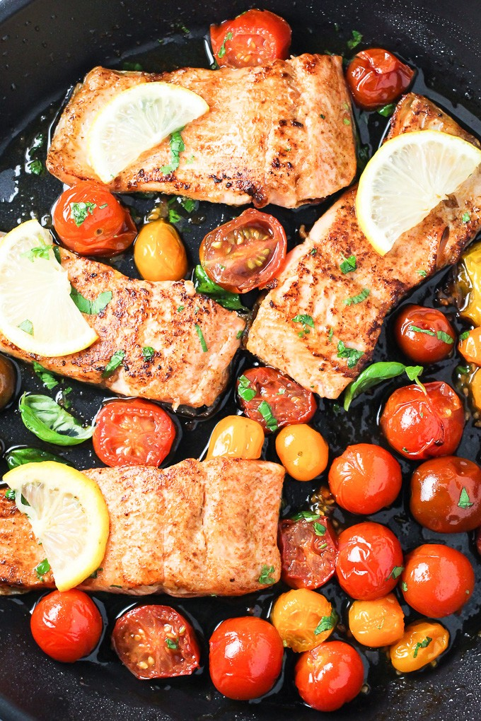 A top view of the pan fried rainbow trout with red cherry tomatoes and lemon slices in a black pan.