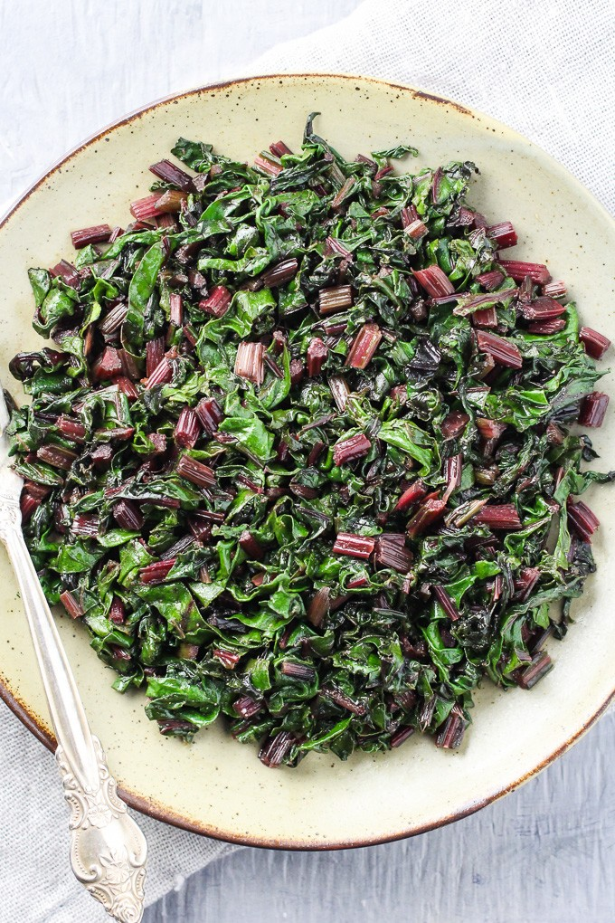 Top view of the sauteed beet greens on a plate with a fork.