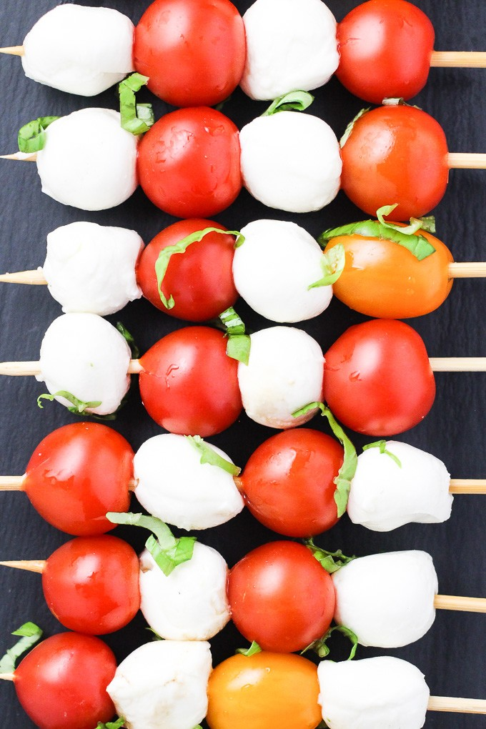 A top-view of small mozzarella cheese balls and cherry tomatoes arranged on toothpicks.