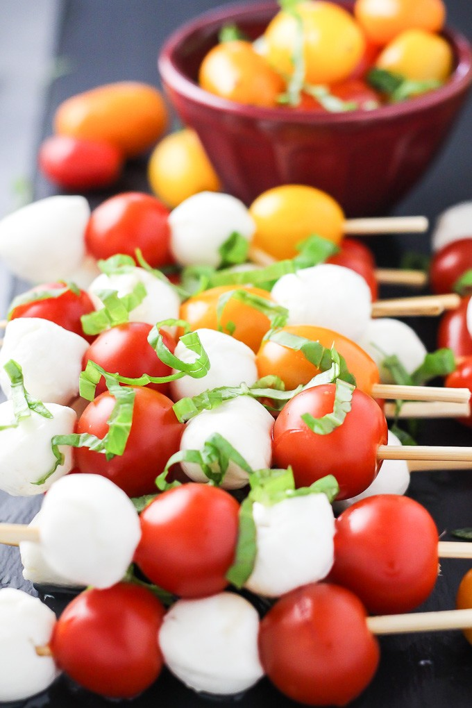 A side-view of the small mozzarella cheese balls and cherry tomatoes arranged on toothpicks.