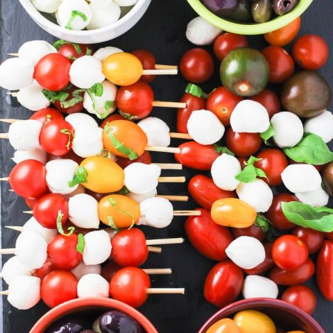 A top view of the caprese appetizer tray with the red and yellow cherry tomatoes, olives, small mozzarella cheese balls, and basil leaves arranged on a cheese board.