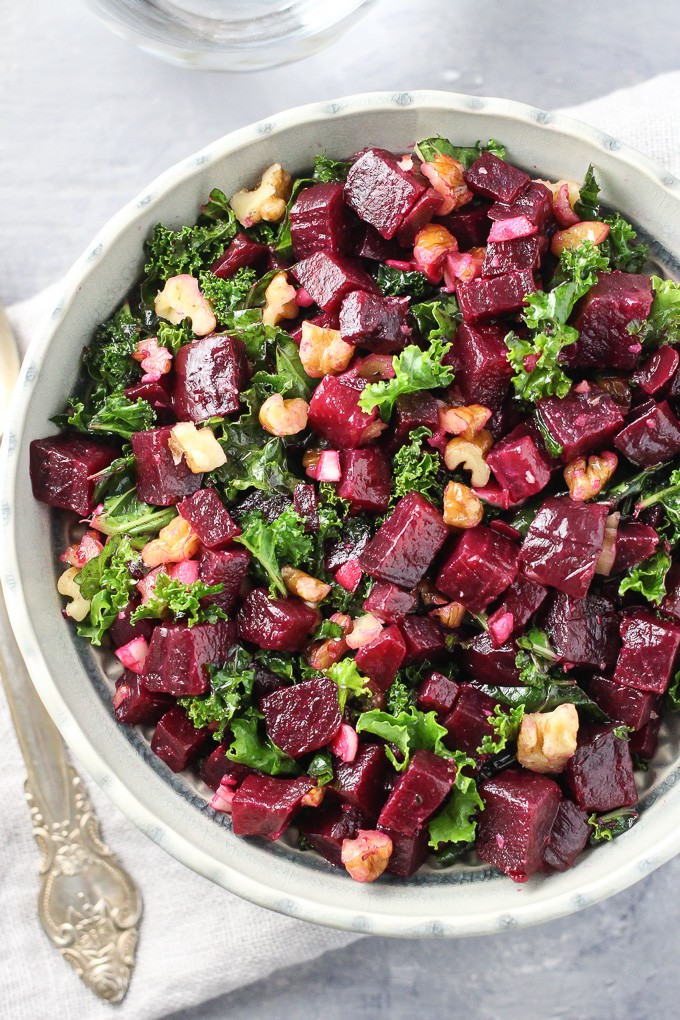 Top view of the detox kale and beet salad in a grey bowl on a grey board.