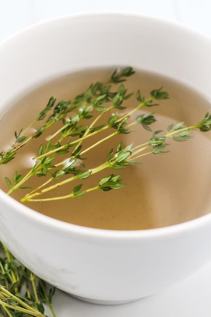 A side-view of a white teacup with the thyme tea and a few thyme sprigs in it.