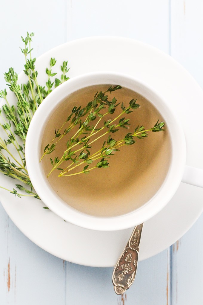 How to Make Thyme Tea: Top-view of a white teacup with a thyme tea in it standing on a white saucer.