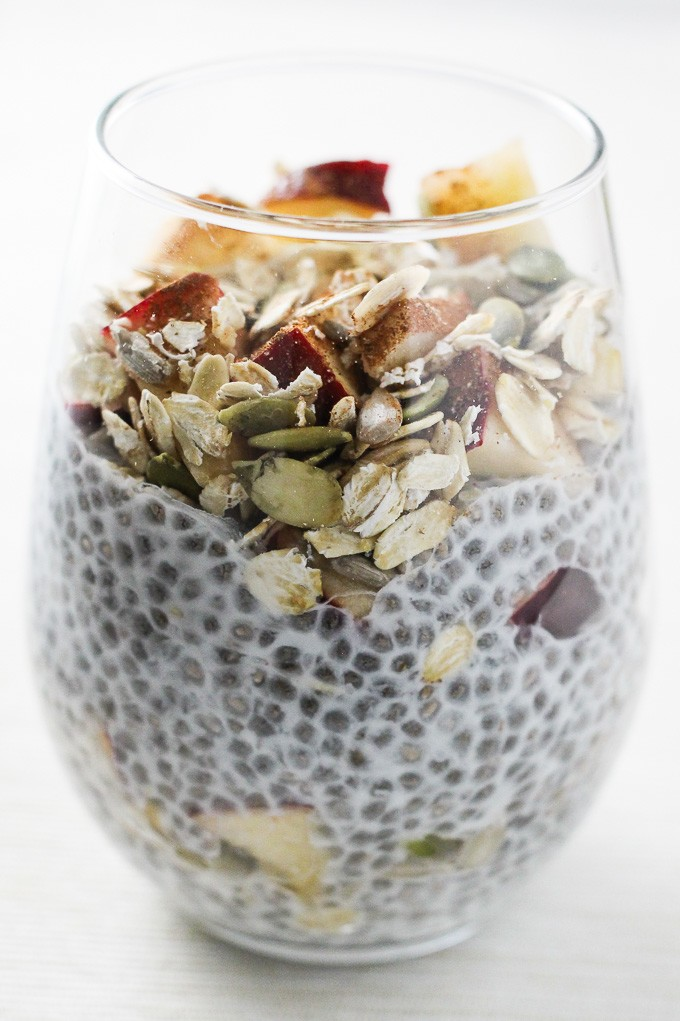 A close-up side view of the apple cinnamon chia pudding breakfast parfait in a glass.