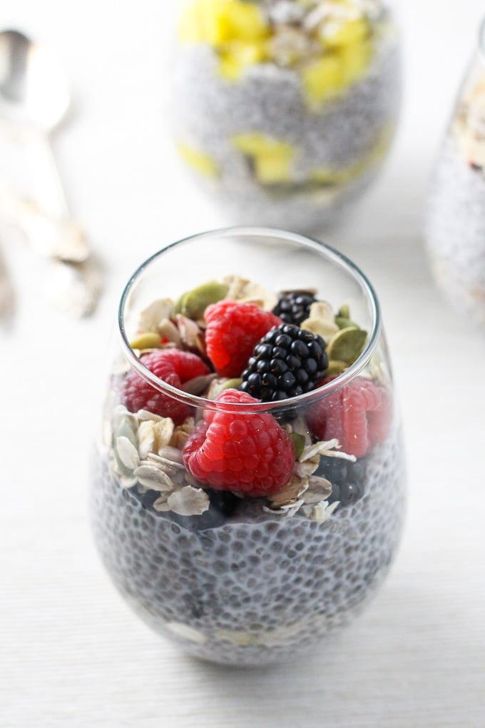 A side view of the chia pudding breakfast parfait in a glass, topped with berries..