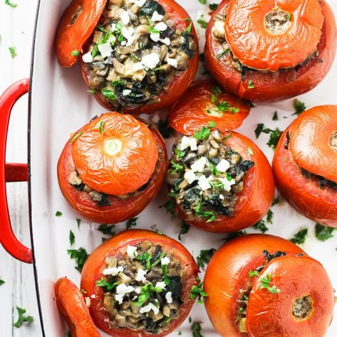A top-view of vegetarian stuffed tomatoes in a white baking dish with red handles.