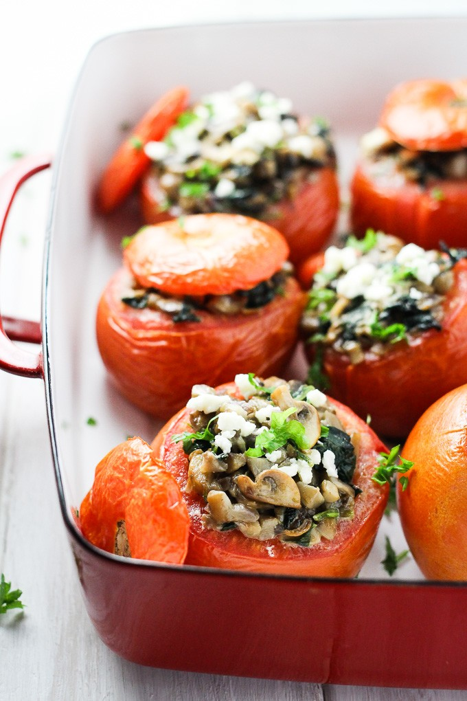 A side-view close up shot of the vegetarian stuffed tomatoes topped with mushrooms, feta, and chopped parsley. All in a red baking dish.