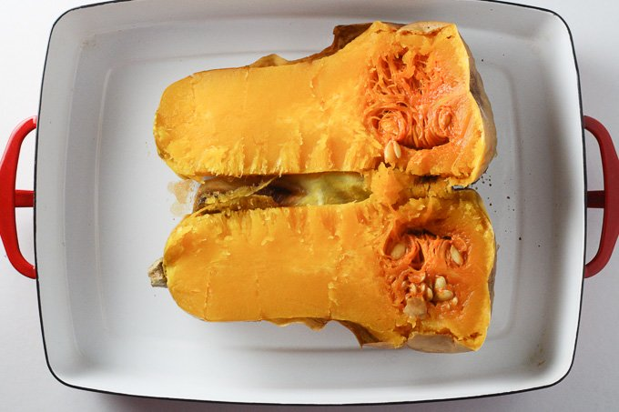 How to Cook Butternut Squash: A top view of a cooked butternut squash cut lengthwise inside a white baking dish.