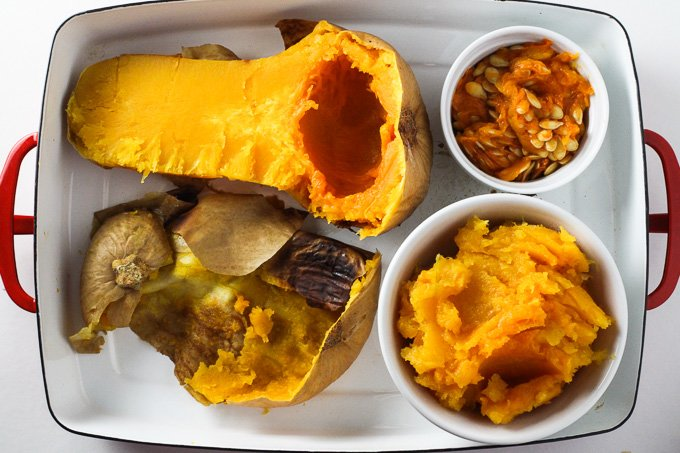 How to Cook Butternut Squash: One half of a cooked butternut squash, a small dish with butternut squash seeds with pulp, skin of a cooked butternut squash, and a small dish with butternut squash puree, all placed inside a baking dish.