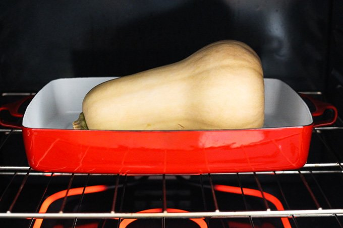 A butternut squash in a red baking dish inside an oven.