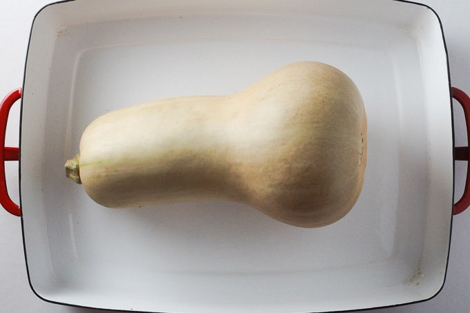 A top view of a butternut squash in a white baking dish.