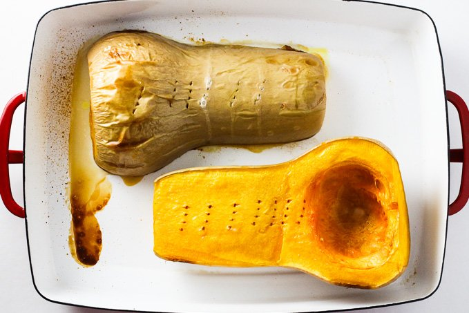 Top view of two cooked butternut squash halves inside a baking dish.