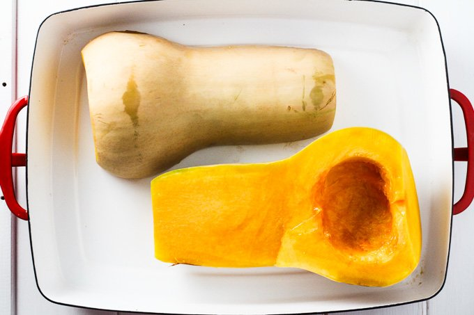 Top view of two butternut squash halves in a white baking dish.