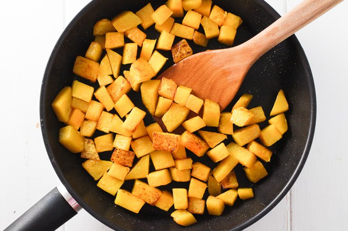Top view of sauteed butternut squash cubes in a black pan with a wooden spatula in the middle.