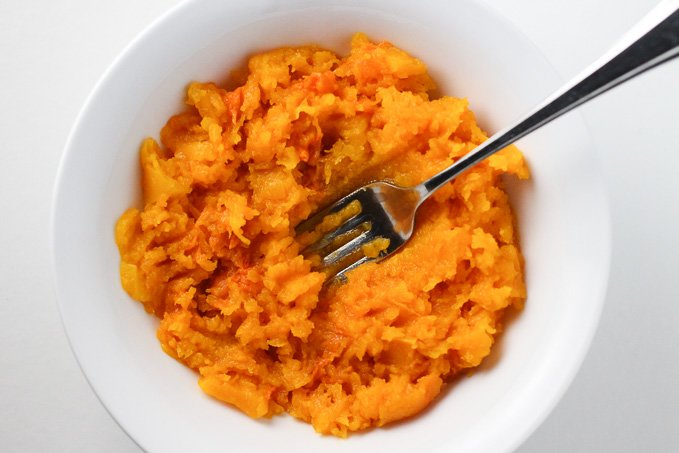Butternut squash puree in a white dish with a fork in the middle.