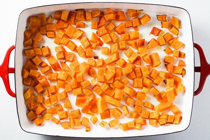 Top view of roasted butternut squash cubes in a baking dish.