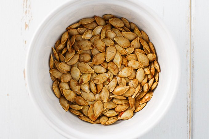Top view of roasted butternut squash seeds in a white bowl.