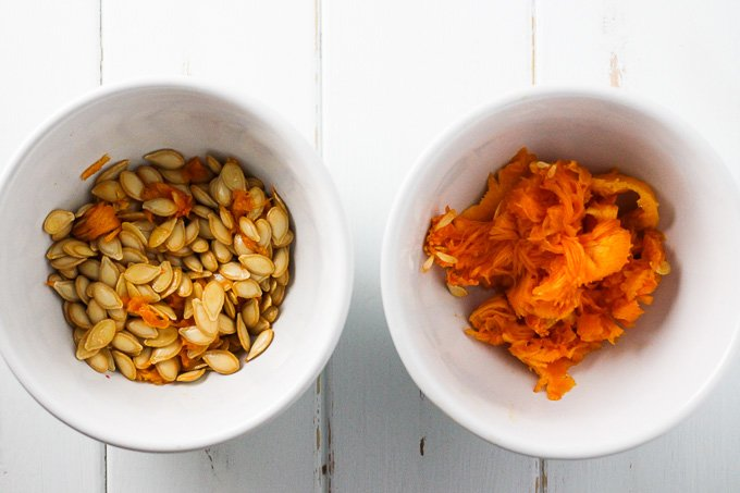 Top view of a white bowl with butternut squash seeds and a bowl with butternut squash pulp.