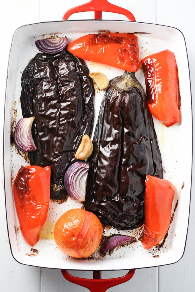 Roasted eggplant, tomato, red pepper, onion, and garlic in a baking dish.