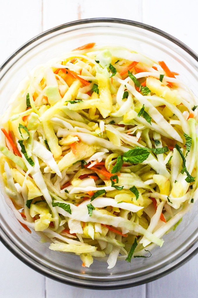 Crunchy pineapple coleslaw in a glass bowl, top view.
