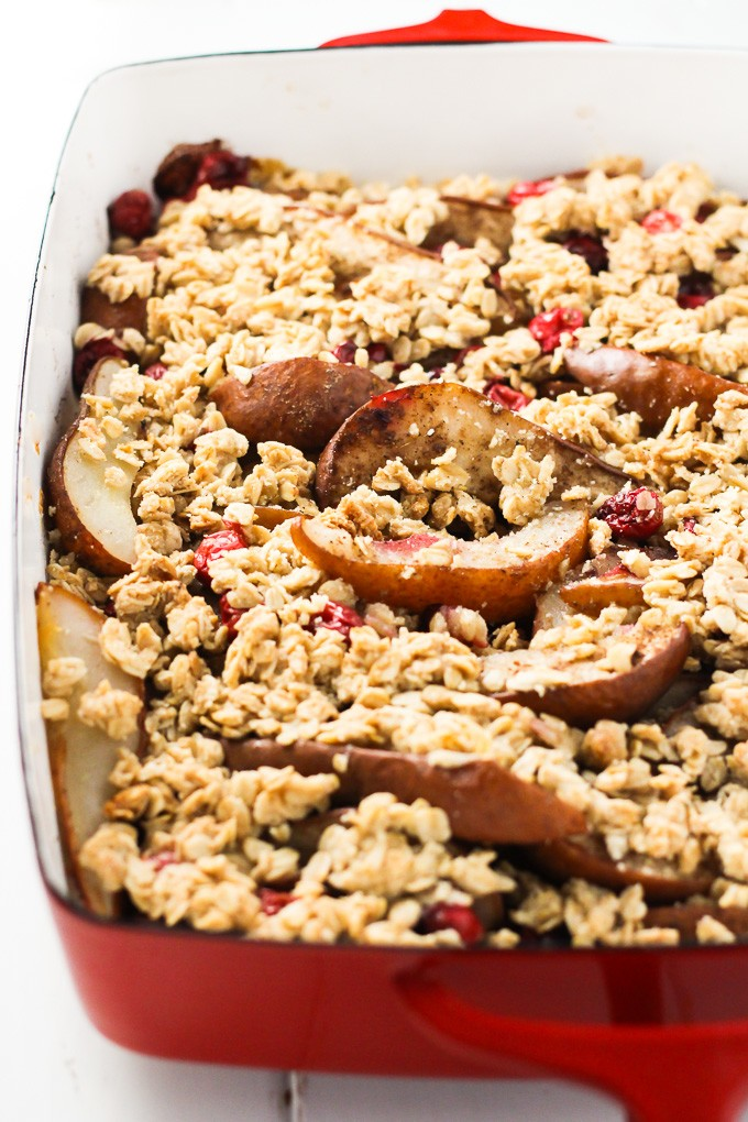 A close-up side view of the pear cranberry crisp in a red baking dish.