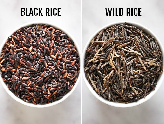Black rice in a small bowl on the left vs. wild rice in a small bowl on the right.