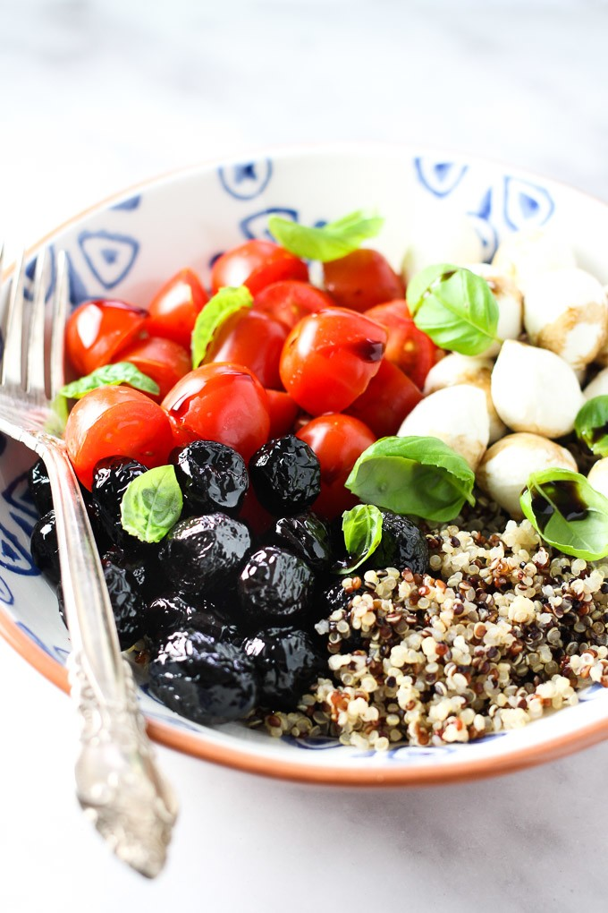 Caprese quinoa bowl with a silver fork on the left.