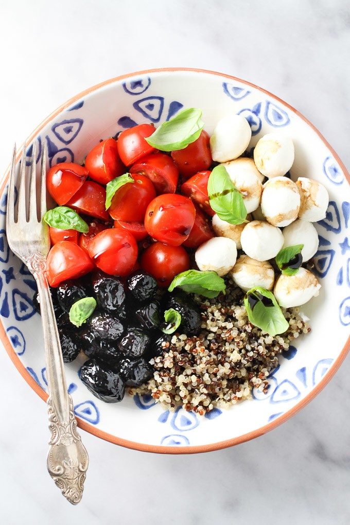 Caprese quinoa bowl with red cherry tomatoes, white bocconcini cheese, black olives, basil leaves and quinoa in a bowl with a silver fork on the left.