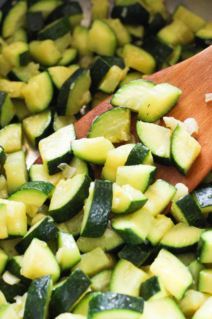 Close up of zucchini slices being tossed with a wooden spatula.