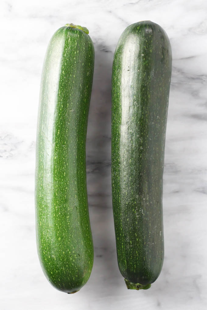 Two fresh zucchini on marble background.