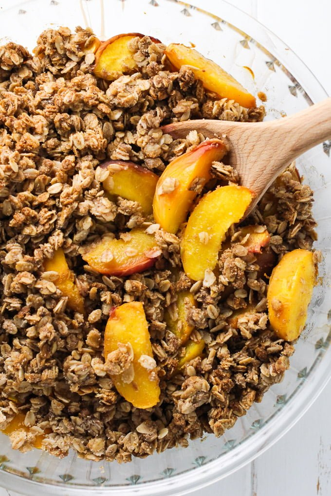 Healthy peach crisp in a round baking dish.