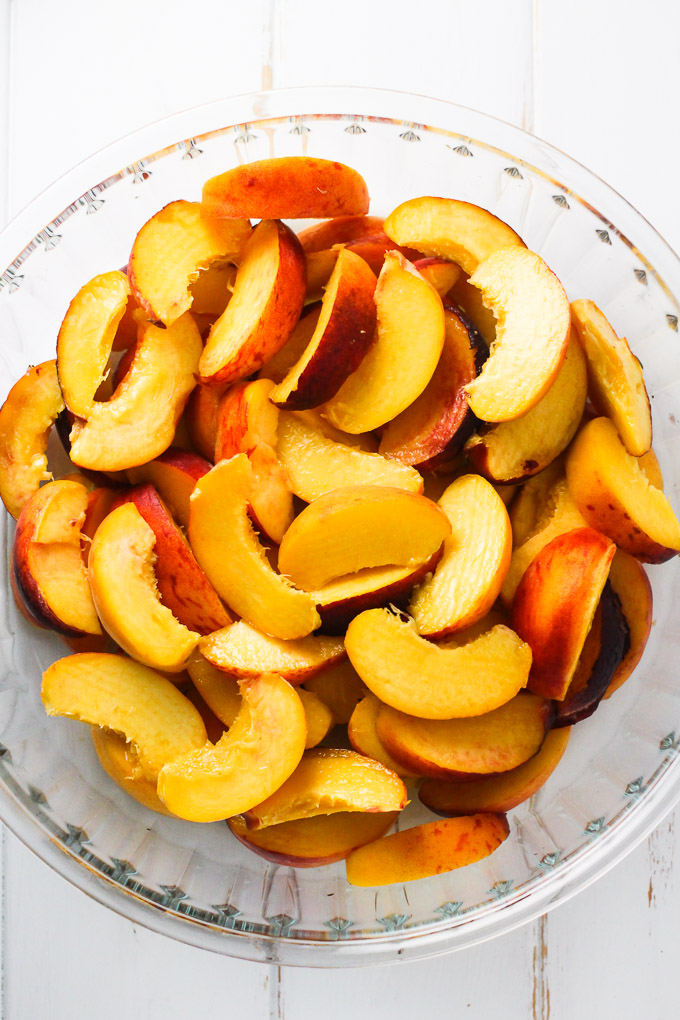 Peach slices in a glass baking dish standing on a white background.