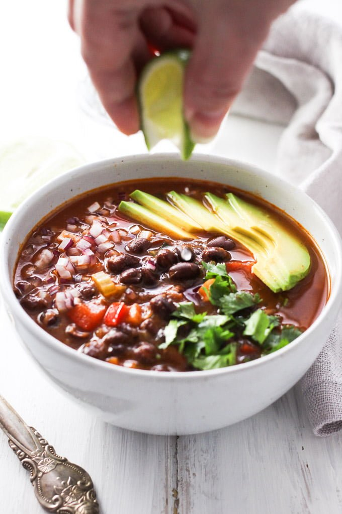 A bowl of canned black bean soup garnished with avocado, onion, fresh cilantro and lime juice.