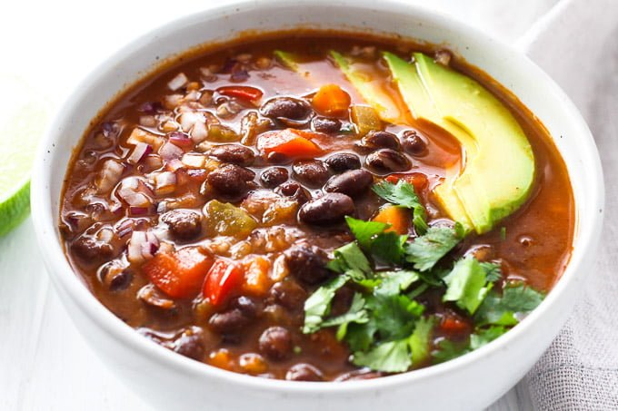 A bowl of black beans soup garnished with avocado, cilantro, and onion. Side view.