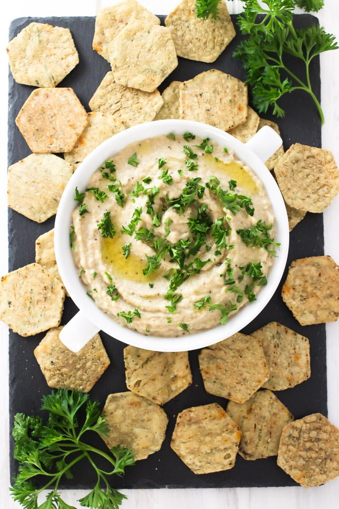 Creamy baba ganoush in a bowl, garnished with chopped parsley. Served with crackers.