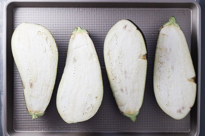 Eggplants on a baking sheet. Cut in half lengthwise. Cut side up.