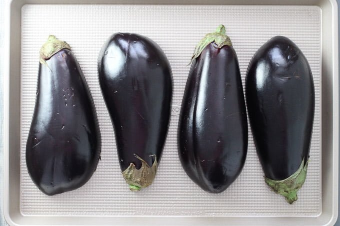Eggplants on a baking sheet. Cut in half lengthwise. Cut side down.