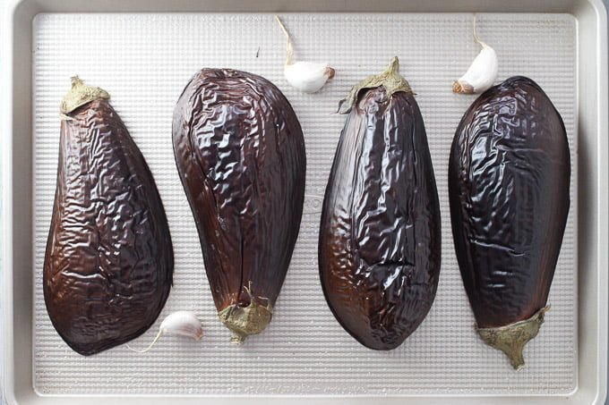 Roasted eggplants and garlic cloves on a baking sheet.