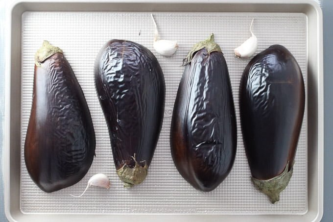 Slightly broiled eggplants on a baking sheet with three garlic cloves.