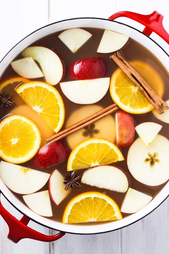 Hot apple cider in a pot. Garnished with orange and apple slices, star anise, and cinnamon sticks. Top view.