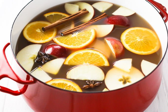 Hot apple cider in a pot. Garnished with orange and apple slices, cinnamon sticks, and star anise.